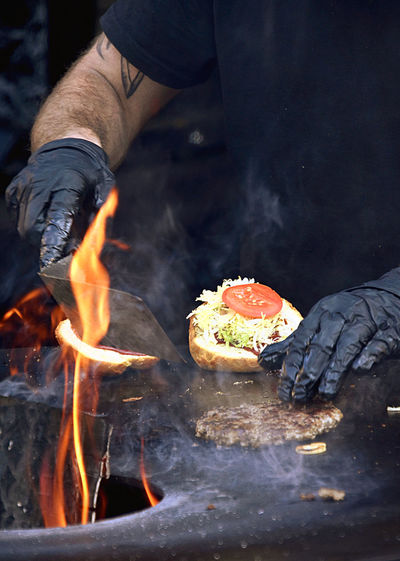 Midsection of man preparing food on barbecue grill