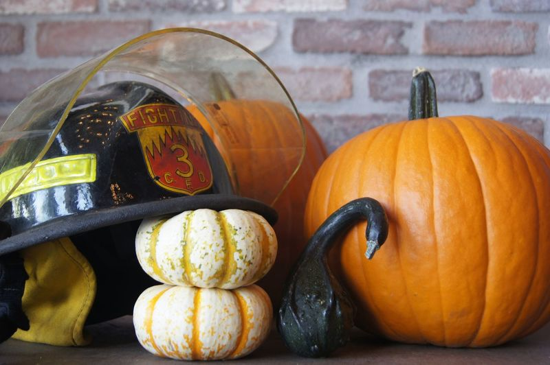 Close-up of pumpkins and helmet on table at home