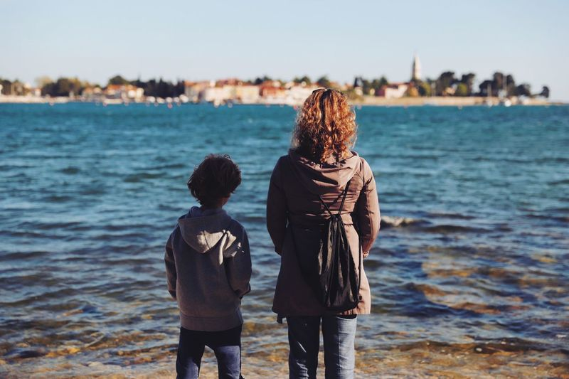 Seaside mother and son bonding Water Rear View Sea Two People Real People Beach Leisure Activity Togetherness Focus On Foreground Men Land Nature Child Sky Family Women Warm Clothing Bonding Outdoors Day