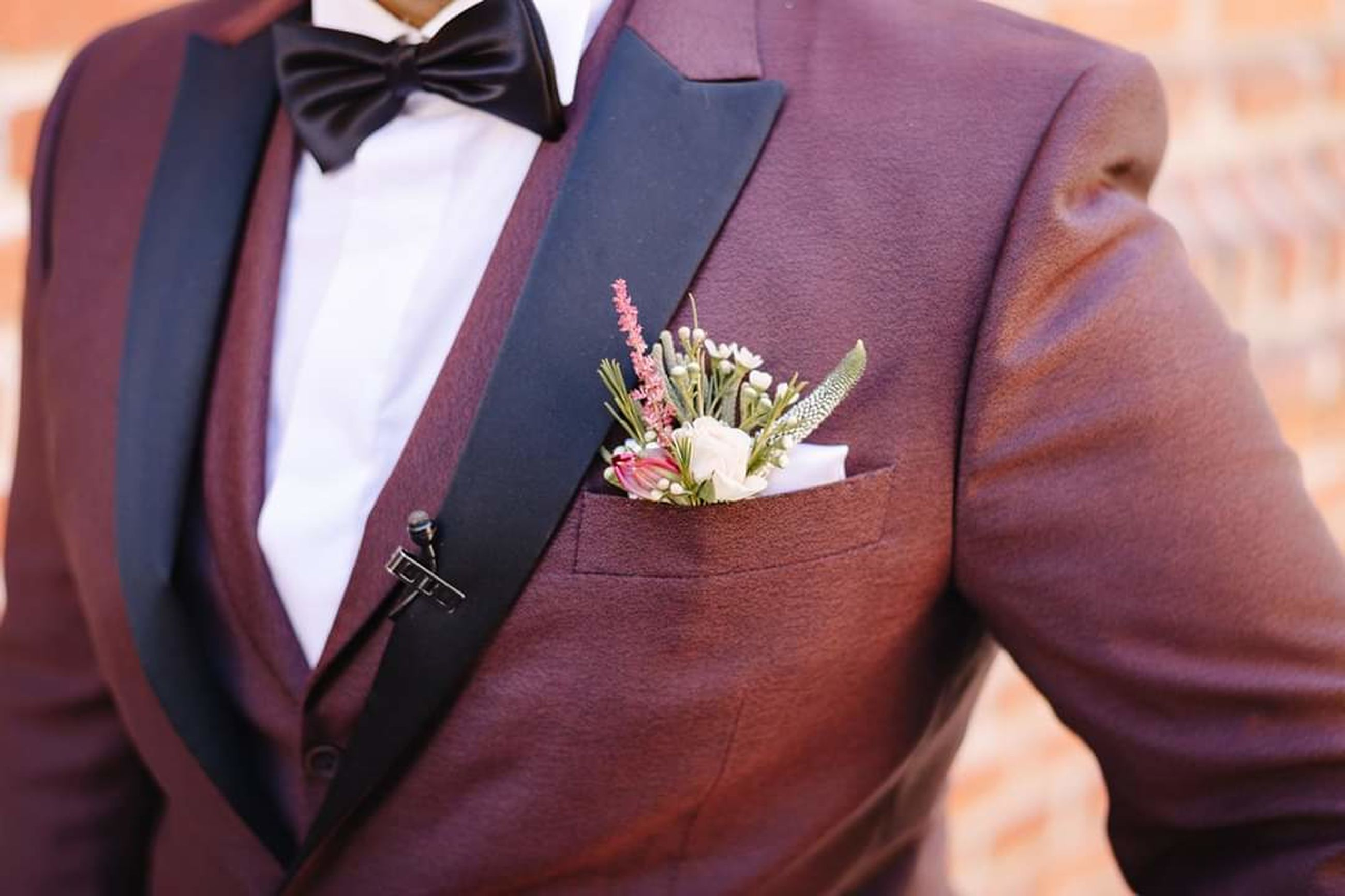 suit, midsection, flower, life events, bride, well-dressed, wedding, clothing, event, men, married, flowering plant, celebration, adult, newlywed, real people, bridegroom, formalwear, standing, business, positive emotion, flower arrangement, couple - relationship, wedding ceremony