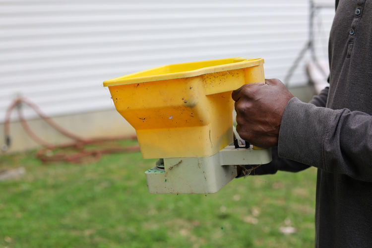 Close-up of person hand holding yellow paper outdoors