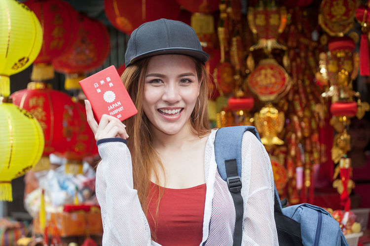 Portrait of beautiful woman holding japanese passport against traditional lanterns in city