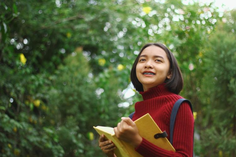 Smiling teenage girl standing at park