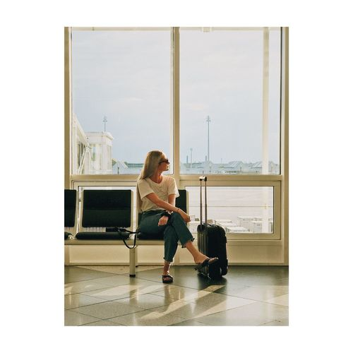 Waiting to leave. Flight Travel Travel Destinations Airport Women One Person Full Length Young Women Real People Young Adult Lifestyles Adult Females Sitting Day Indoors