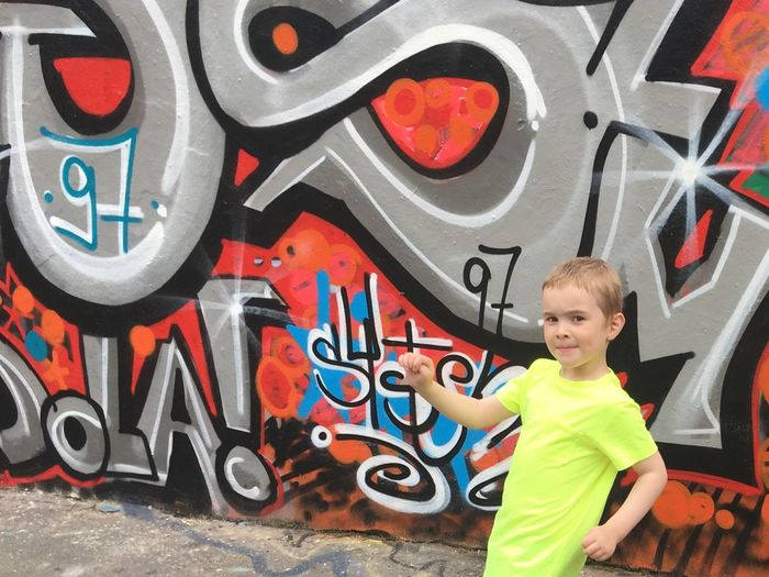 Portrait of boy standing against multi colored graffiti on wall
