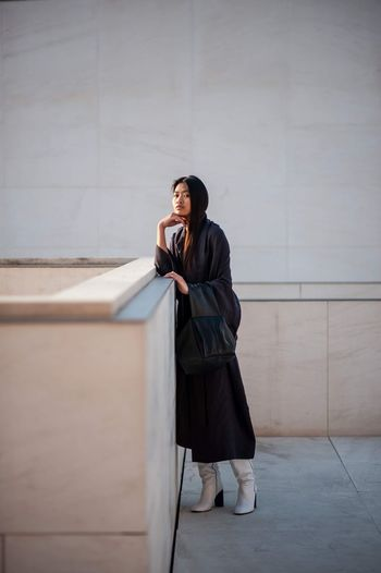 The Minimalist - 2019 EyeEm Awards EyeEm Selects One Person Real People Young Adult Full Length Leisure Activity Lifestyles Wall - Building Feature Young Women Architecture Built Structure Standing Casual Clothing Building Exterior Young Men Clothing Beautiful Woman Looking Looking Away Day Warm Clothing