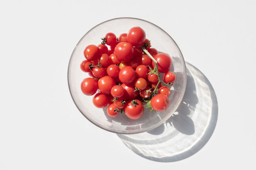 Cherry tomatoes in glass bowl with hard shadow from above Bowl Cherry Tomato Close-up Directly Above Food Food And Drink Freshness Fruit Healthy Eating High Angle View Indoors  No People Plate Red Ripe Still Life Studio Shot Temptation Tomato Vegetable Wellbeing White Background