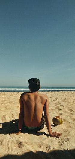 Rear view of shirtless man sitting on beach