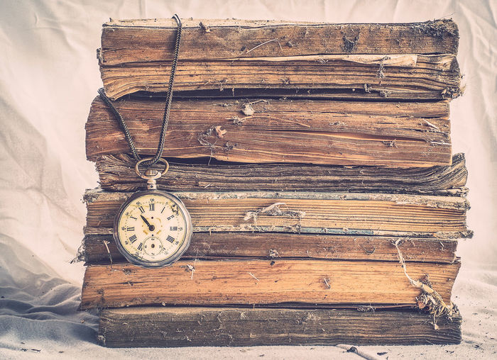 Close-up of pocket watch on old stacked books