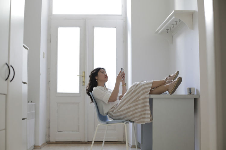 Woman using smart phone while sitting on chair at home