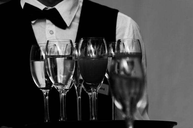 Midsection of waiter serving drinks