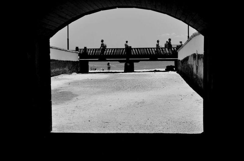 Silhouette people on bridge against sky in city