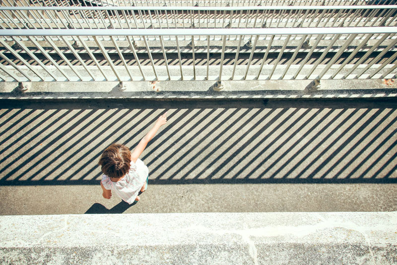 High angle view of girl standing by railing