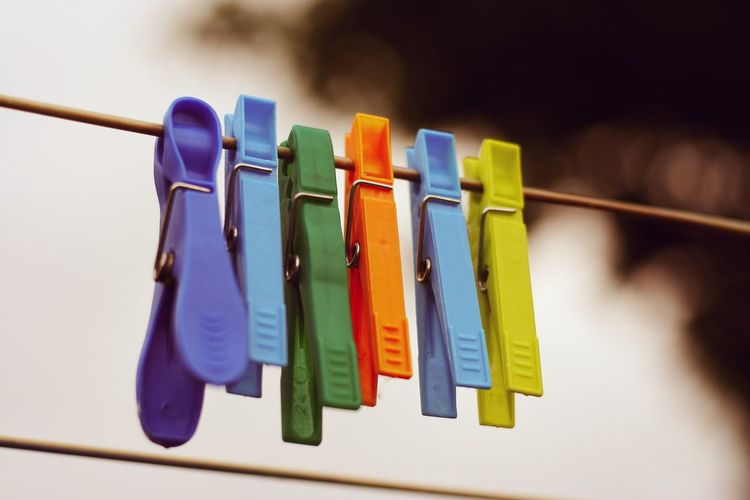 Close-Up Of Colorful Pegs Hanging On Clothesline