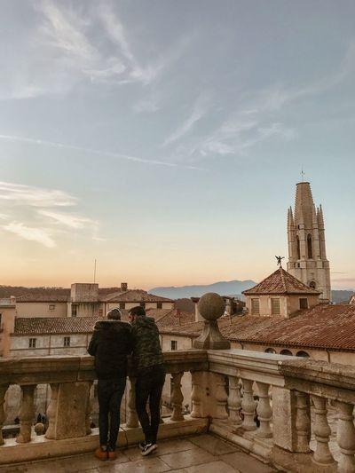 Rear view of people standing by buildings against sky