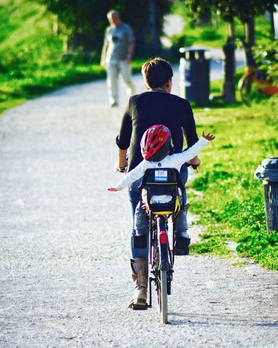Rear view of boys riding bicycle on road