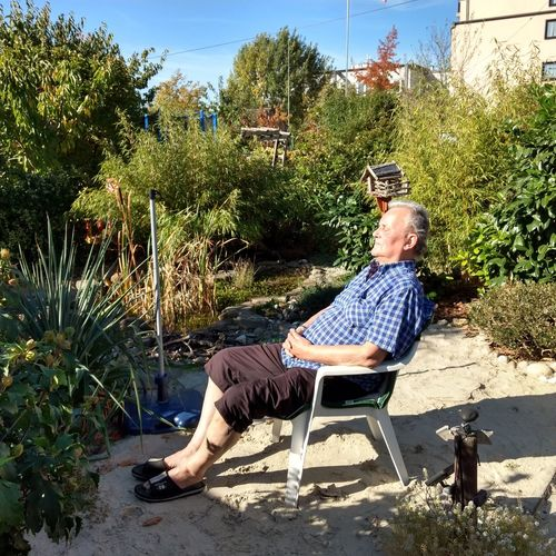 Man sitting on chair against plants