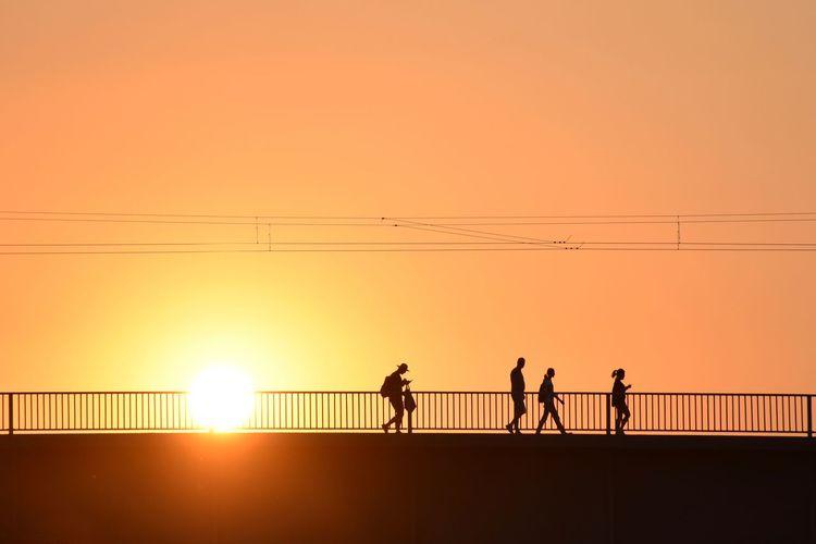 Silhouette people walking on bridge against orange sky