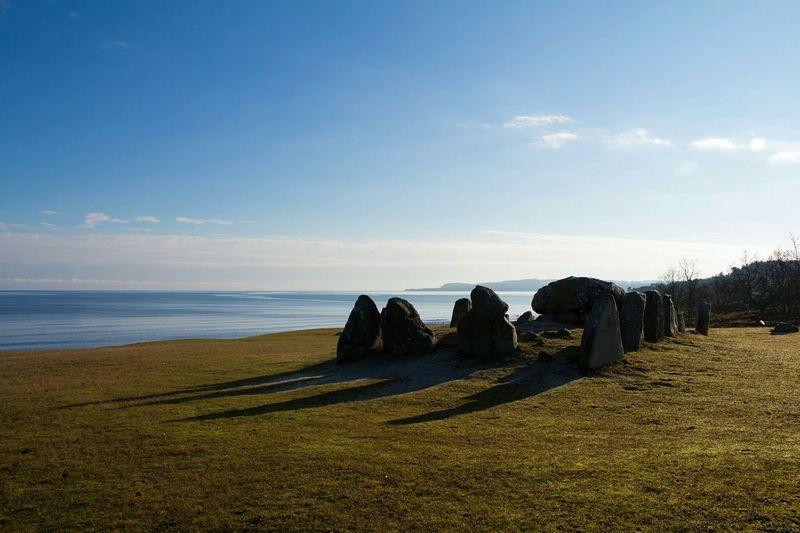 Rocks on shore against blue sky