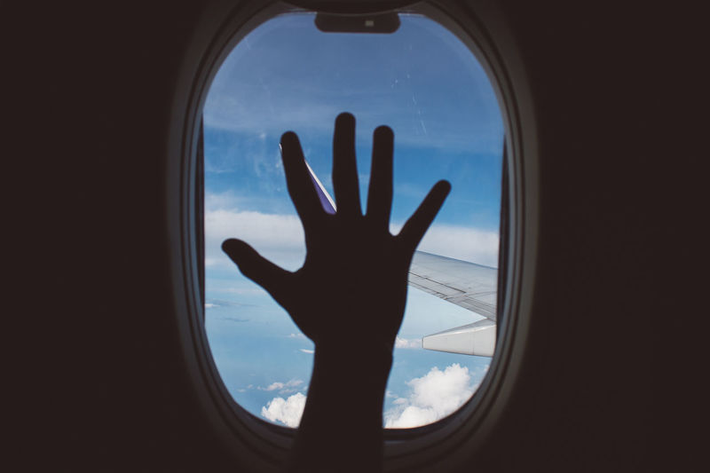 Silhouette of person hand against sky seen through window