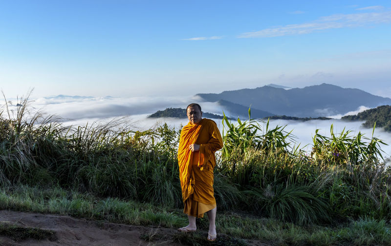 Portrait of monk standing on mountain against sky