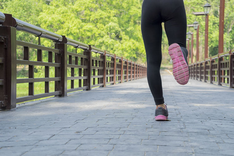 Low section of woman running on footbridge