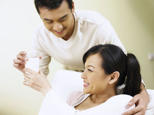 husband offering a glass of milk to his wife Asian  Care Love Black Hair Bonding Calcium Casual Clothing Cheerful Happiness Healthy Eating Healthy Food Husband And Wife Living Room Milk Offer Pregnancy Pregnant Relaxation Smiling Sofa Taking Care Two People Young Adult Young Men Young Women