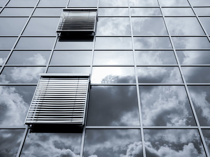 Low angle view of modern building with cloudy sky reflecting