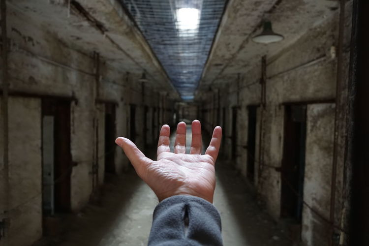 Cropped hand of man gesturing in corridor