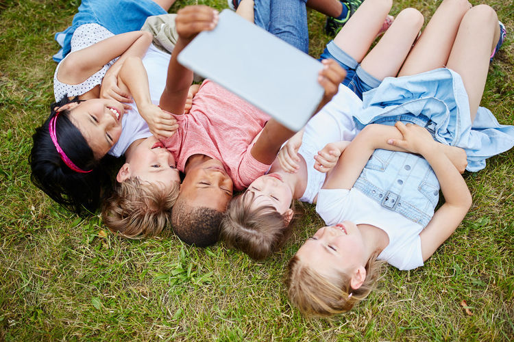 Friends Using Digital Tablet While Lying On Field In Park