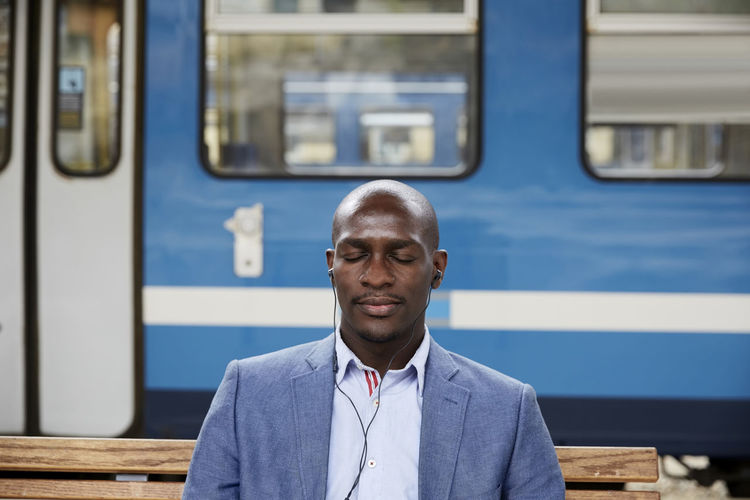 Portrait of man standing by train