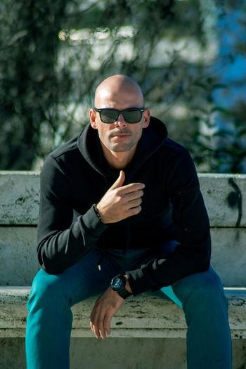 Portrait of man wearing sunglasses sitting outdoors
