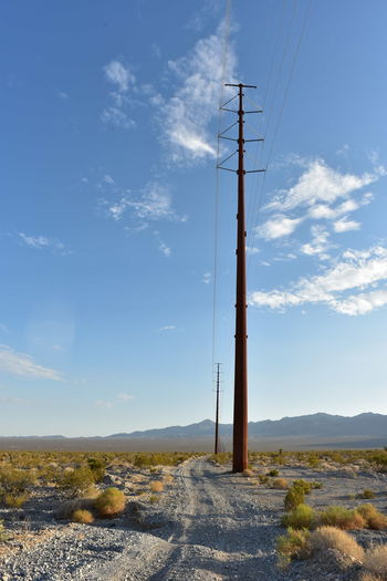 Electrical power poles and power lines along dirt road  power line road in pahrump, nevada, usa