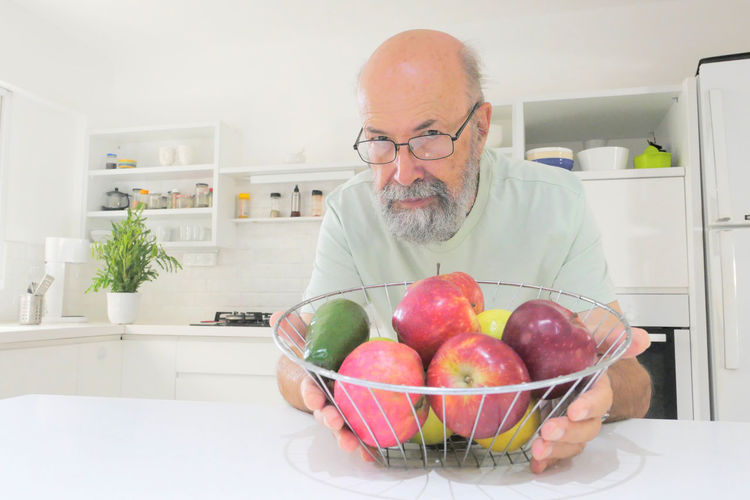 Man holding fruits in plate on table