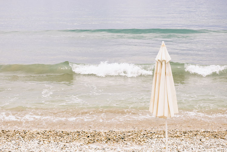 Beach Umbrella Sea Beach Water Wave Nature Holiday Holidays Vacations Sunny Summer Summertime Greece Beach Umbrella Relaxation Summery Backgrounds Background Copy Space Shore Coast Horizon Over Water Tranquil Scene Tranquility Day Scenics - Nature No People Beauty In Nature