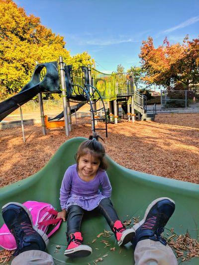 Full length of happy girl riding on swing in park