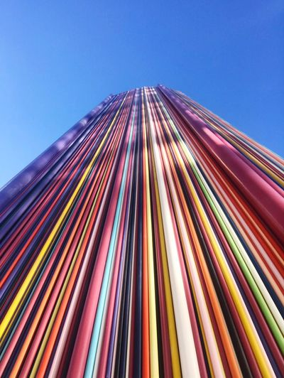 Low angle view of multi colored umbrellas against blue sky