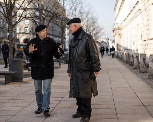 People standing on footpath amidst street