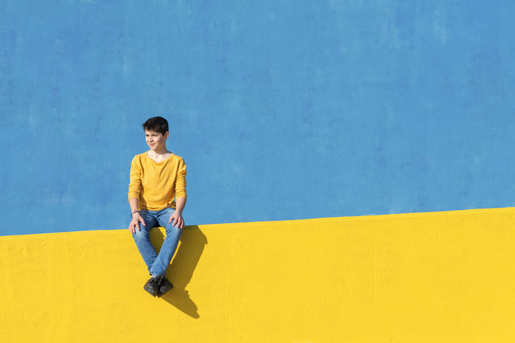 Full length of boy sitting against wall