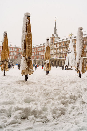 Rear view of people walking on snow covered city against sky