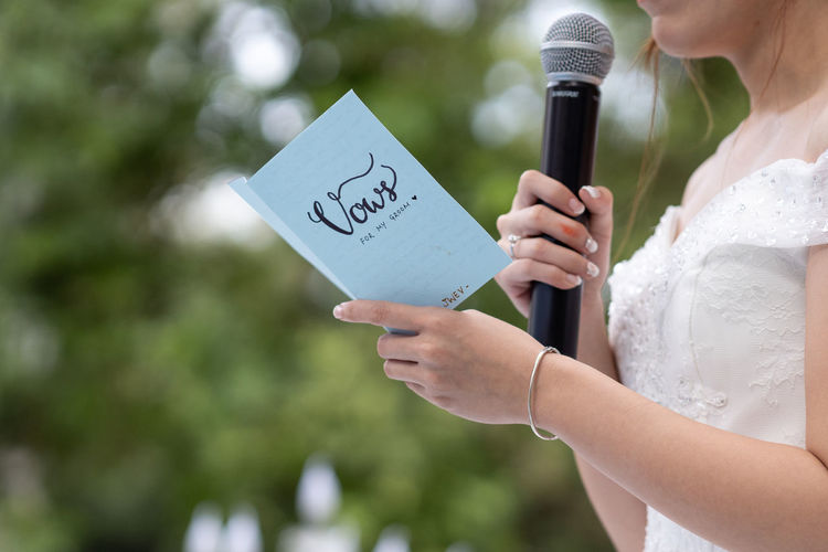 Wedding Adult Bride Celebration Ceremony Communication Day Event Females Focus On Foreground Holding Life Events Message Midsection Newlywed Outdoors Paper People Real People Text Vow Wedding Wedding Ceremony Western Script Women