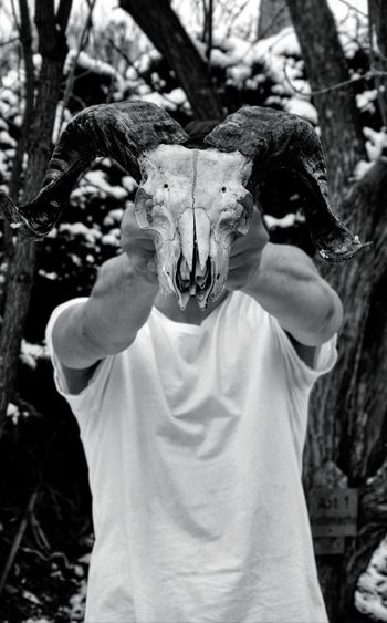 Man holding animal skull while standing against trees