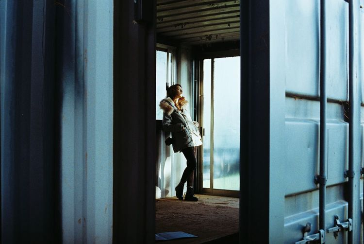 Side view of woman standing by window in building