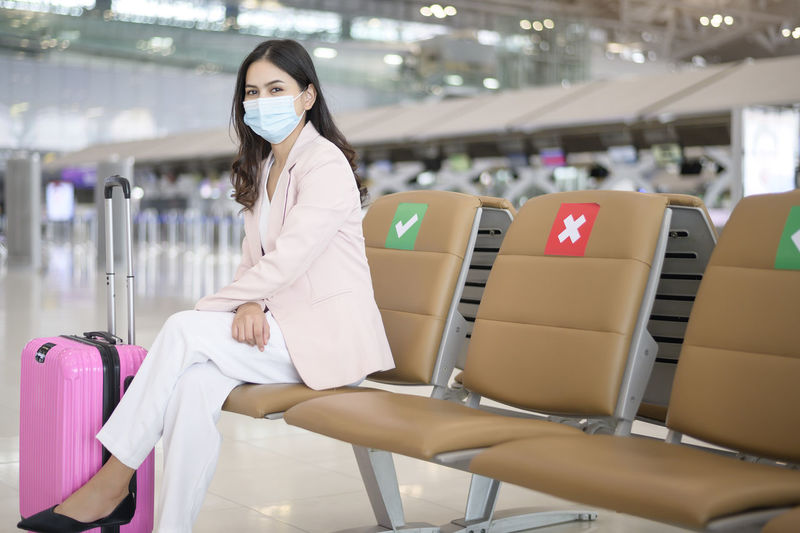 Portrait of businesswoman wearing mask sitting at airport