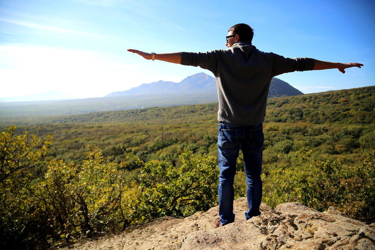 A young man stands on top of a mountain on a large stone. high quality photo