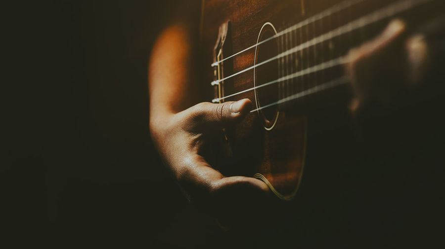 Close-up of hand playing guitar against black background