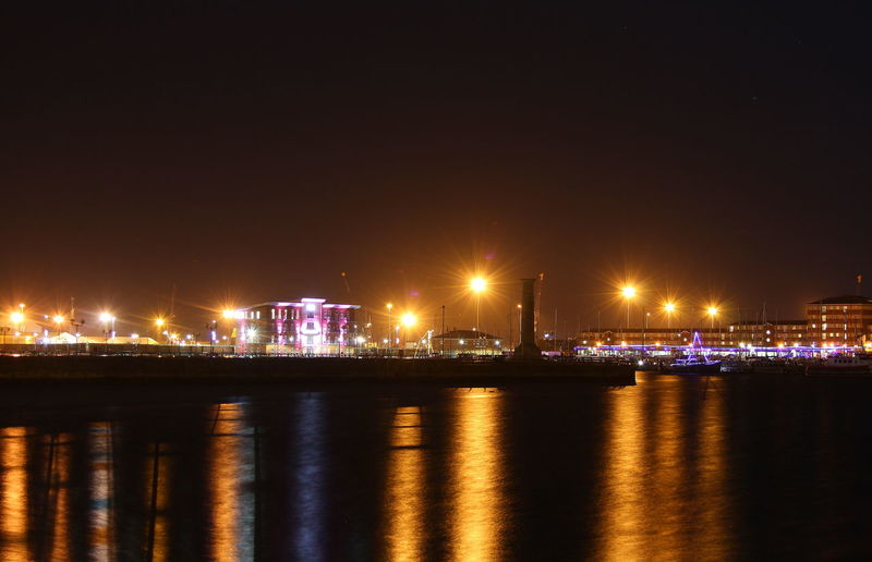 Illuminated City At Waterfront