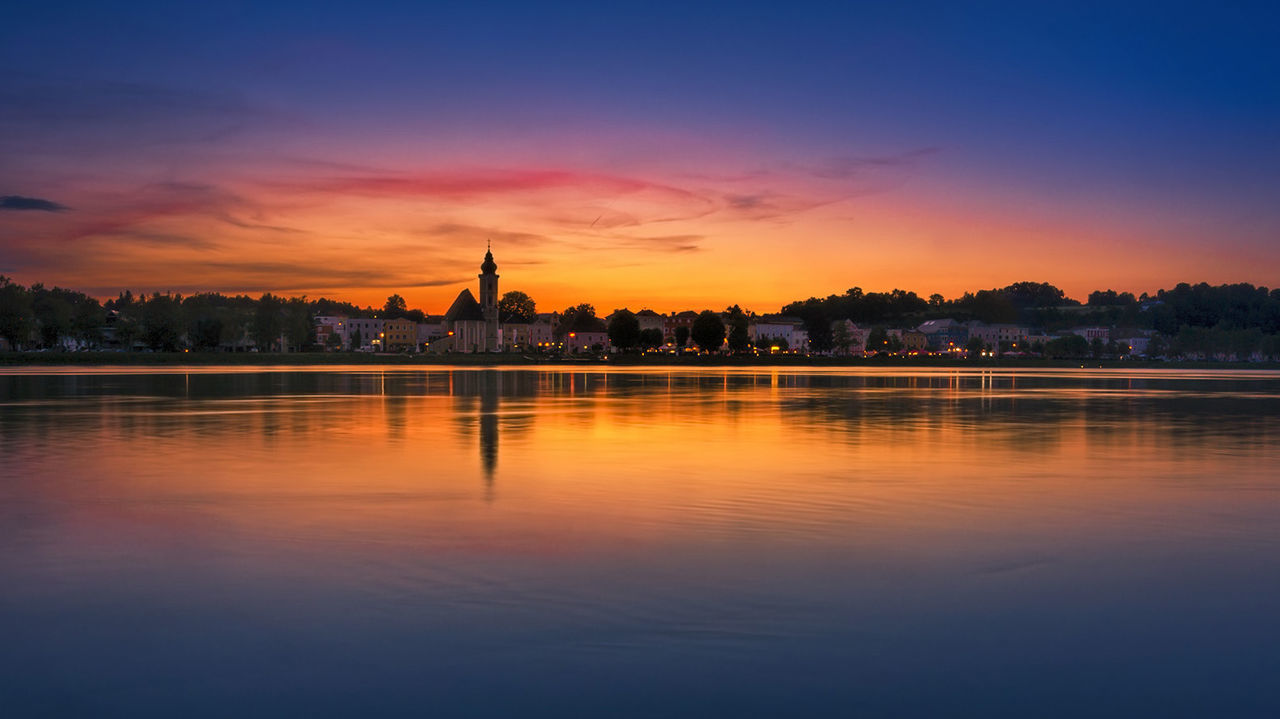 sky, sunset, architecture, built structure, water, reflection, building exterior, waterfront, orange color, nature, silhouette, no people, travel destinations, cloud - sky, religion, beauty in nature, travel, building, river, outdoors