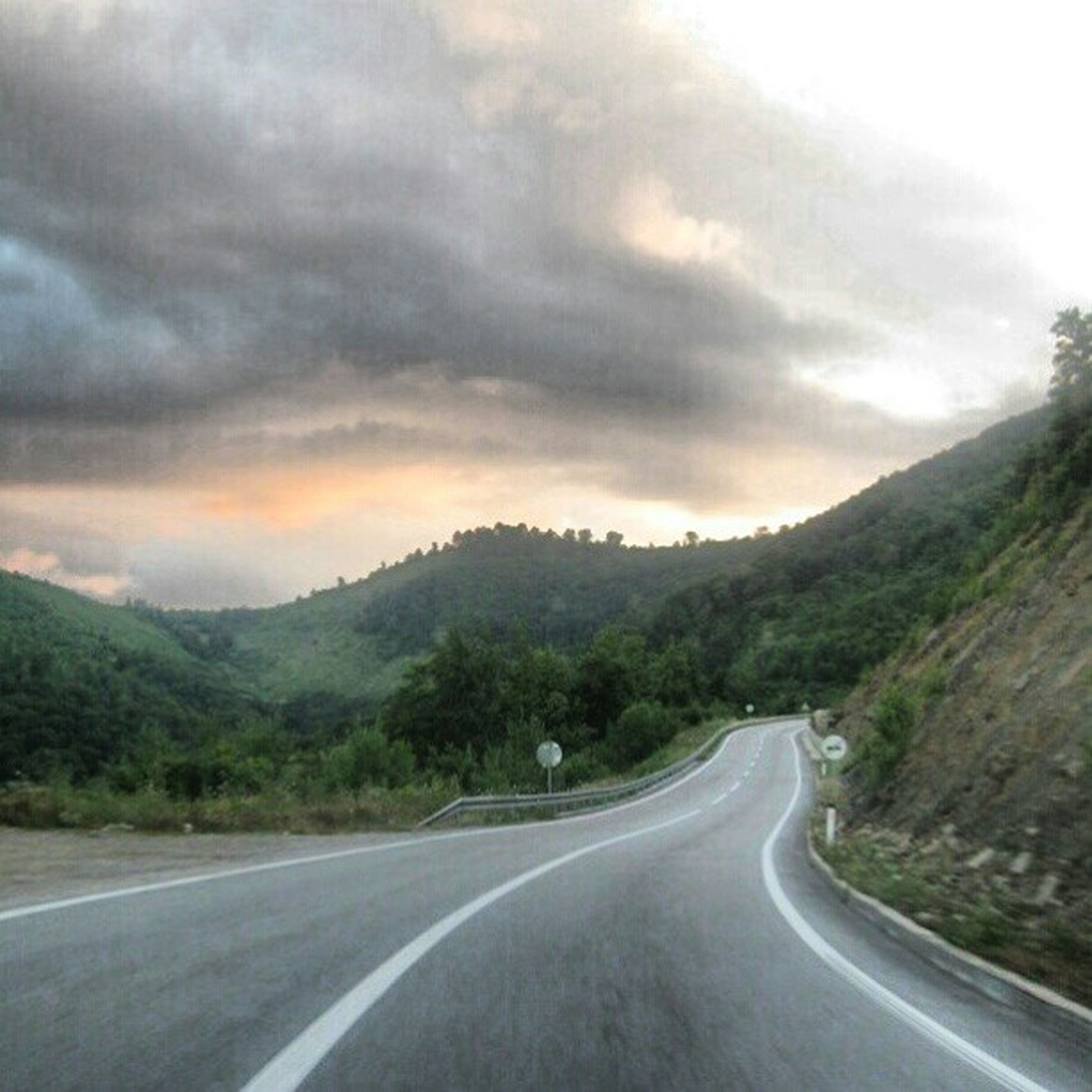 road, the way forward, transportation, mountain, sky, diminishing perspective, country road, road marking, cloud - sky, vanishing point, cloudy, tranquil scene, scenics, tranquility, mountain range, landscape, beauty in nature, nature, empty road, cloud