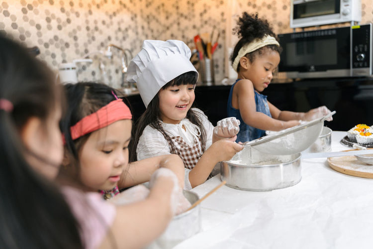 Group of kids are preparing the bakery in the kitchen .Children learning to cooking cookies Kid Kids Childhood Children Child Diversity Friendship Friend Playing Education Learning Offspring Group Of People Girls Domestic Room Togetherness Indoors  Women Kitchen Females Headshot Boys Domestic Kitchen Males  Home Family Looking Domestic Life Preparation  Uniform Innocence Preparing Food
